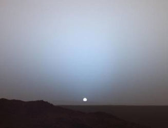 At the horizon, light scattering through the longer column of dust appears blue, as in a smoke-filled room
